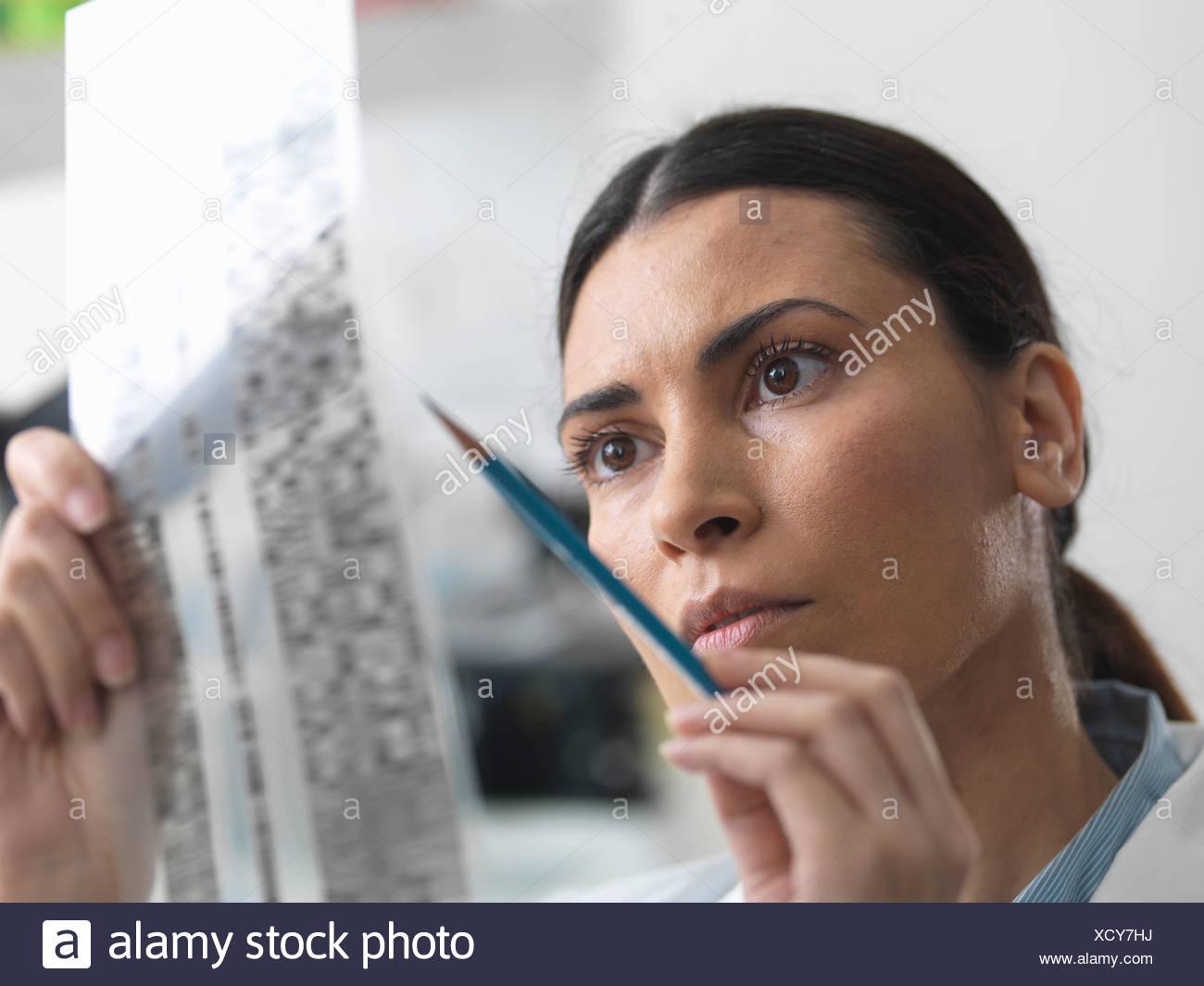 L'examen scientifique des femmes en gel d'ADN pour la recherche génétique en laboratoire Photo Stock