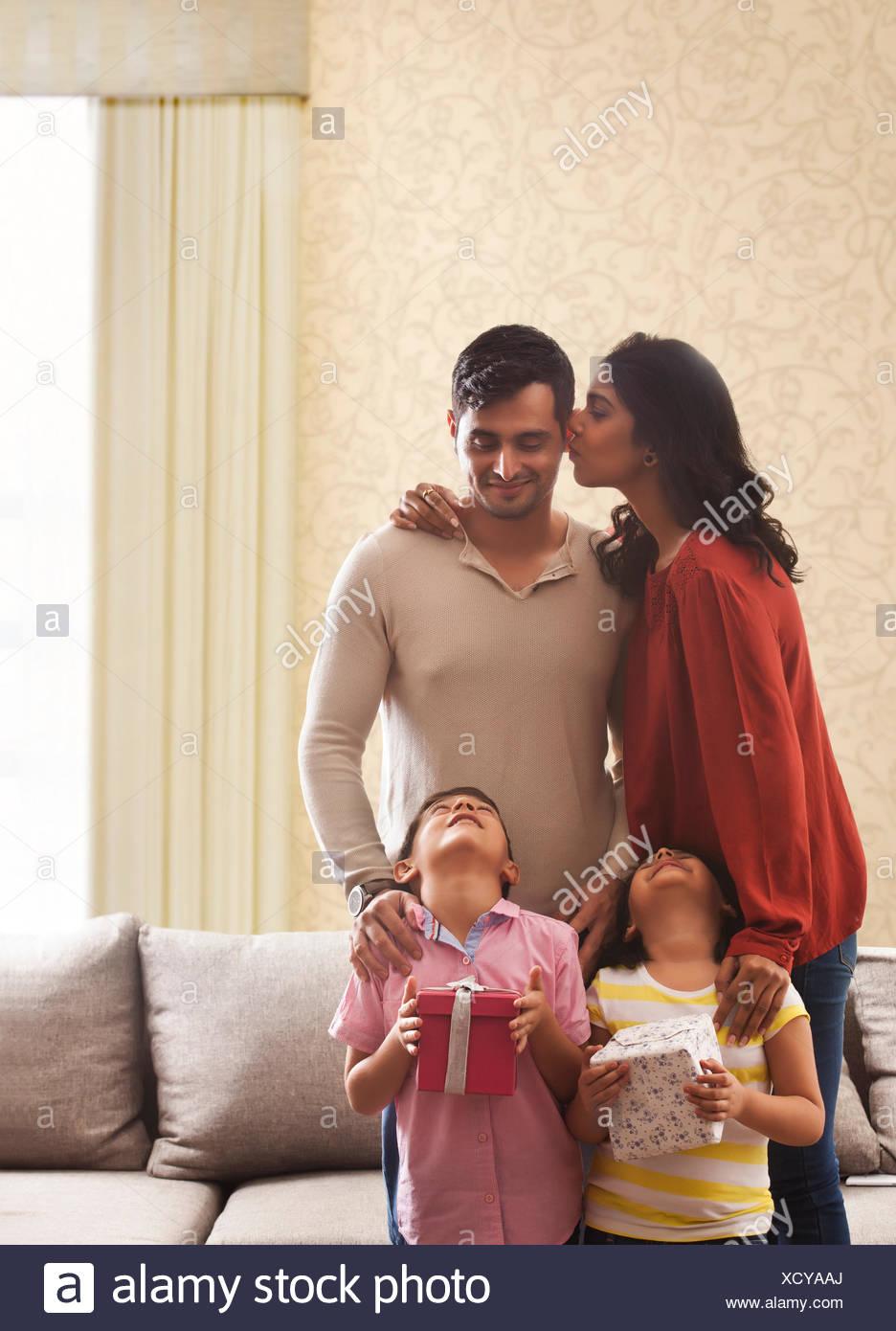 Woman kissing man on cheek, fille et garçon jusqu'à la holding gifts avec retour Banque D'Images