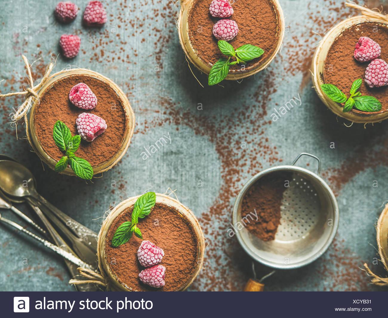 Tiramisu dessert italien fait maison servi dans des verres individuels avec les feuilles de menthe et de poudre de cacao sur fond de béton gris, vue du dessus, les fo Photo Stock