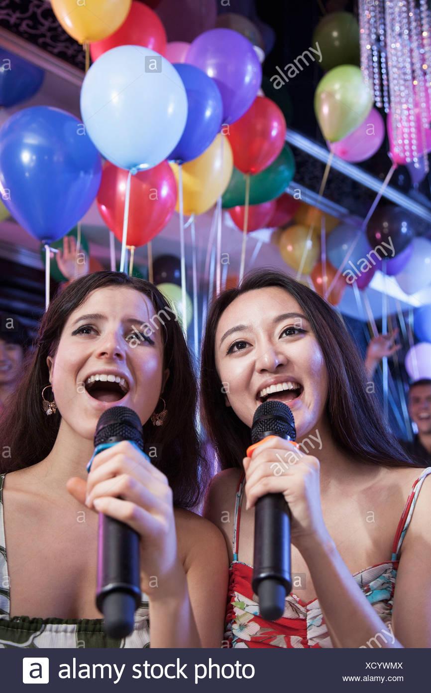 Deux amis holding microphones et chanter au karaoké, des ballons à l'arrière-plan Photo Stock