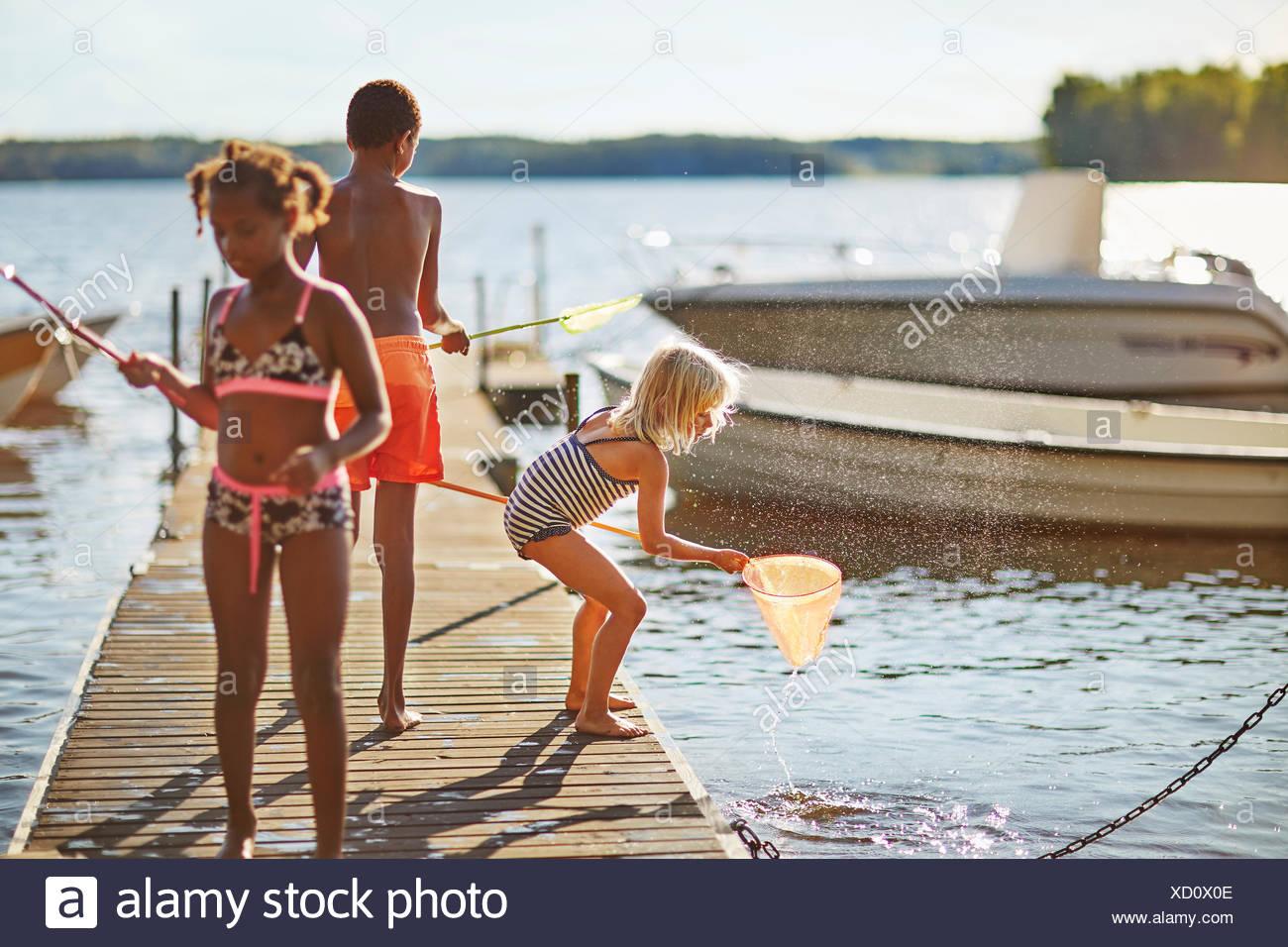 Sur un quai de pêche Enfants Photo Stock