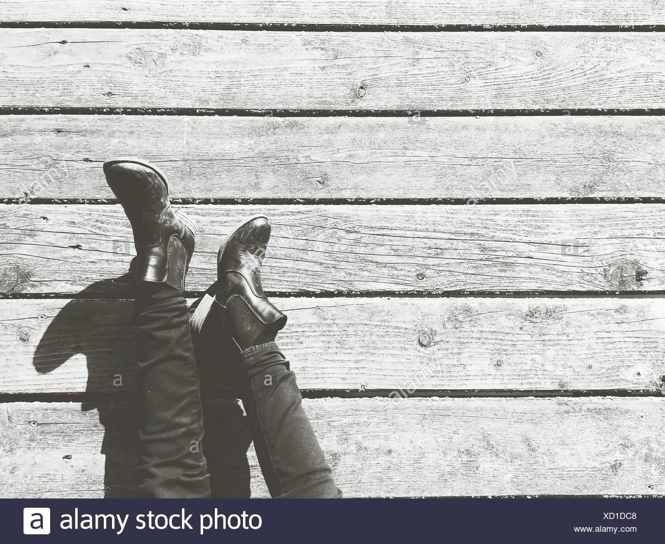 La section basse de l'homme reposant sur bois parquet stratifié Photo Stock