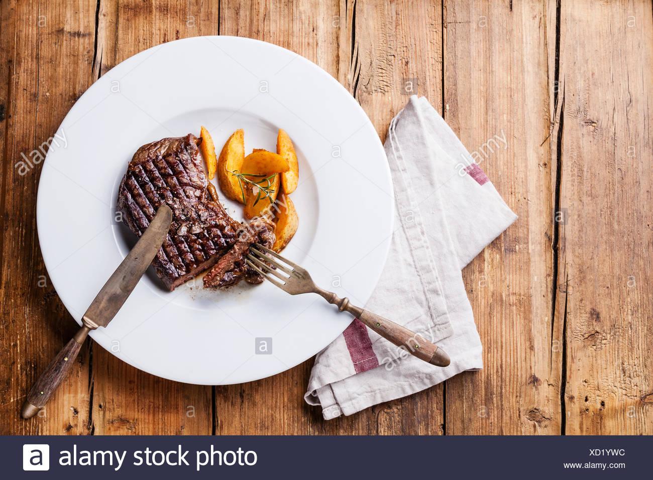 Amérique du Sud grillé Bifteck de boeuf premium avec les quartiers de pommes de terre rôties sur plaque blanche sur fond de bois Photo Stock