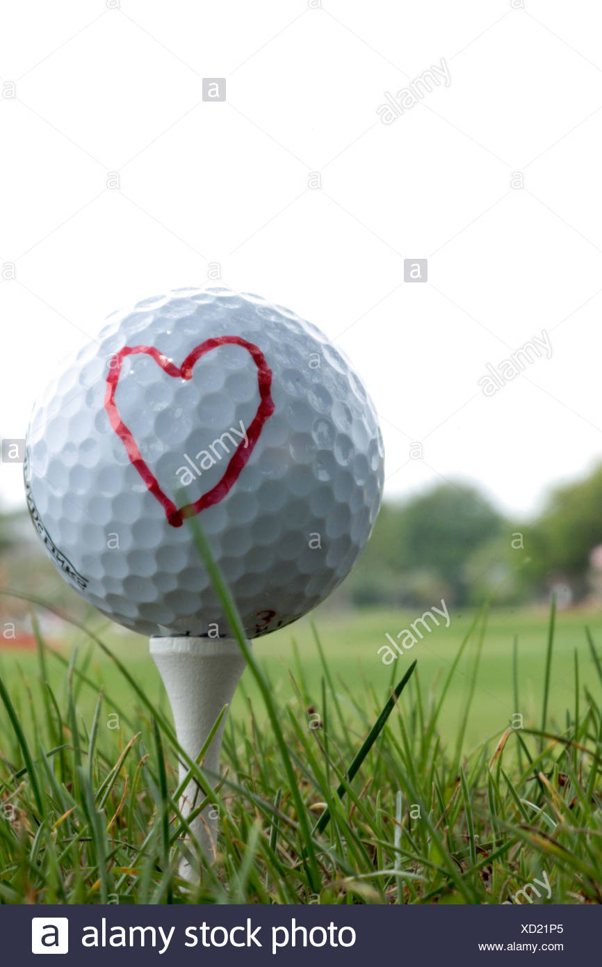 Close-up d'une balle de golf sur un raccord en t avec un cœur dessiné dessus Photo Stock
