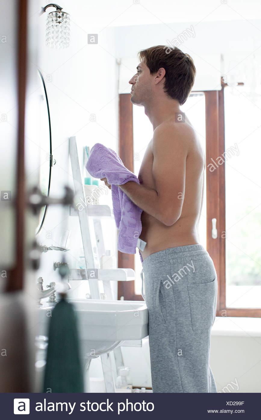 L'homme dans la salle de bains sécher avec une serviette Photo Stock