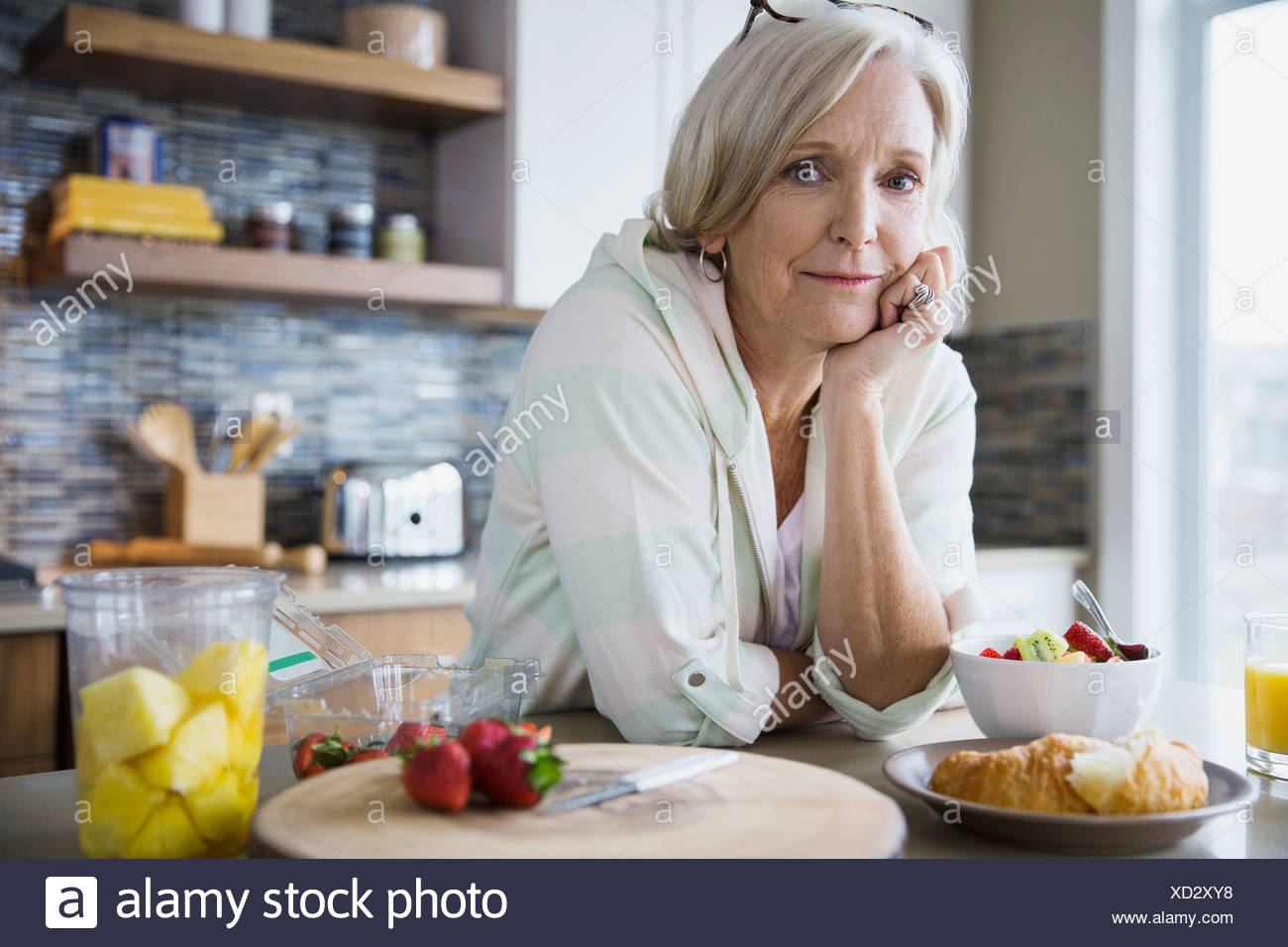 Portrait of woman eating breakfast in kitchen Photo Stock