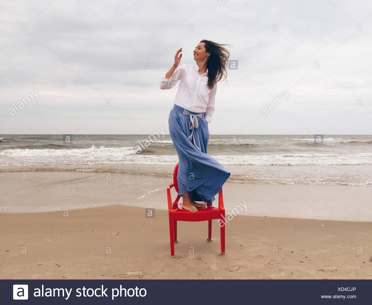 Belle femme debout sur une chaise à la ciel nuageux Photo Stock