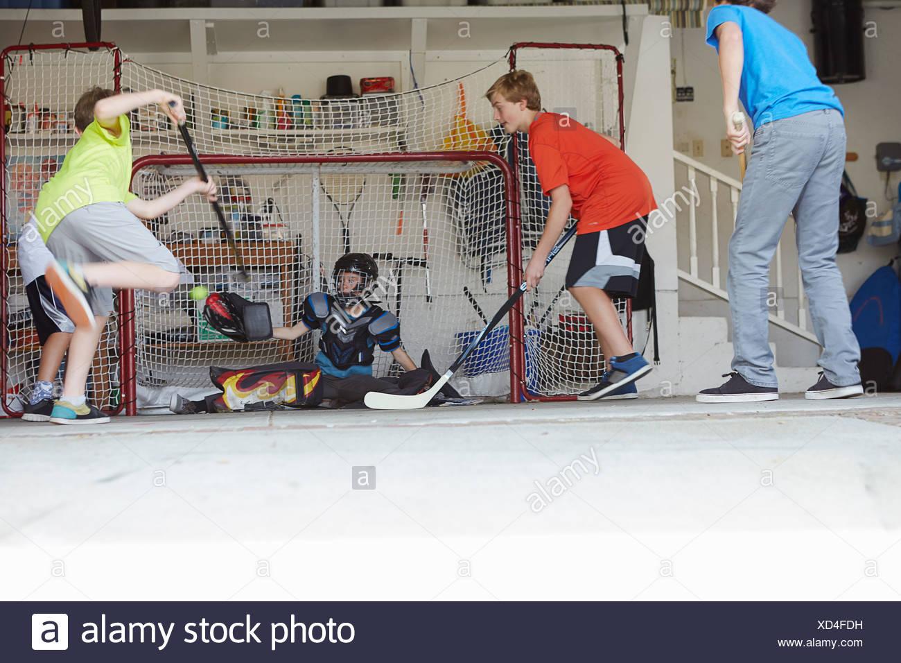 Garçons jouant au hockey dans garage Photo Stock