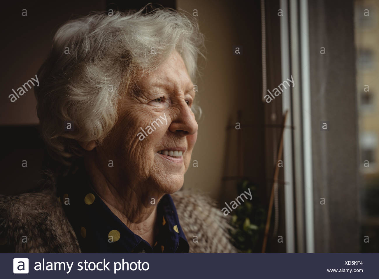 Smiling senior woman looking out de la fenêtre Photo Stock