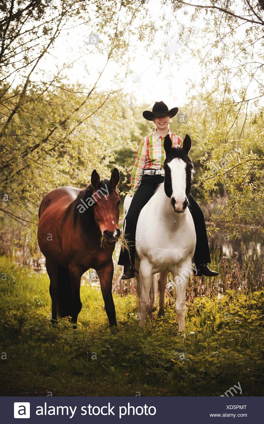 L'ouest femelle cavalier au cheval noir, couleur Tobiano baie, à la tête d'un cheval arabe Shagya, cheval bareback par Photo Stock