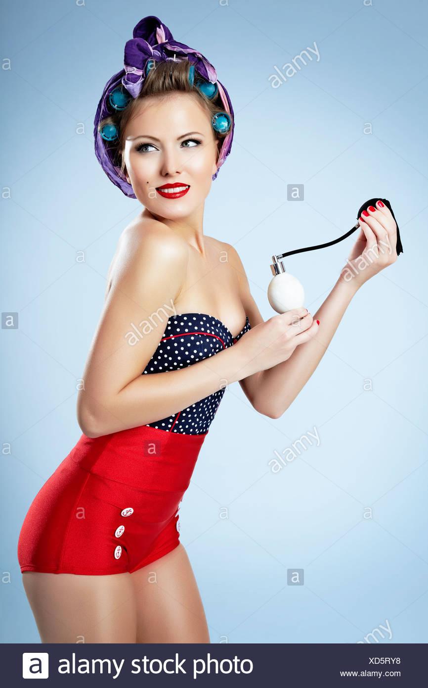 Jeune femme avec les bigoudis, short et un flacon de parfum, pin-up Photo Stock