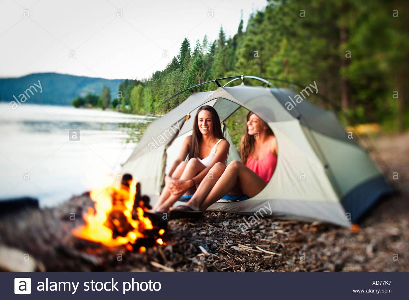 Deux belles femmes rire et sourire assis dans leur tente à côté d'un feu de camp dans l'Idaho. Photo Stock