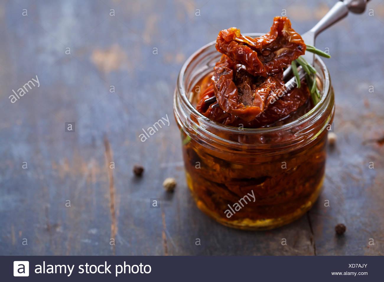 Les tomates séchées en pot sur fond de bois Photo Stock
