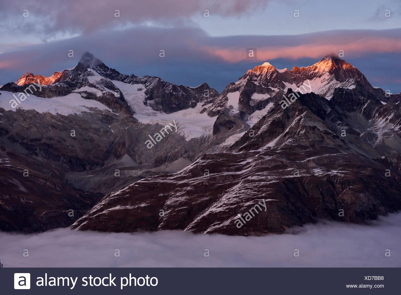 Lever du soleil sur les montagnes voisines à l'est de la majestueuse Matterhorn (hors du champ). Photo Stock
