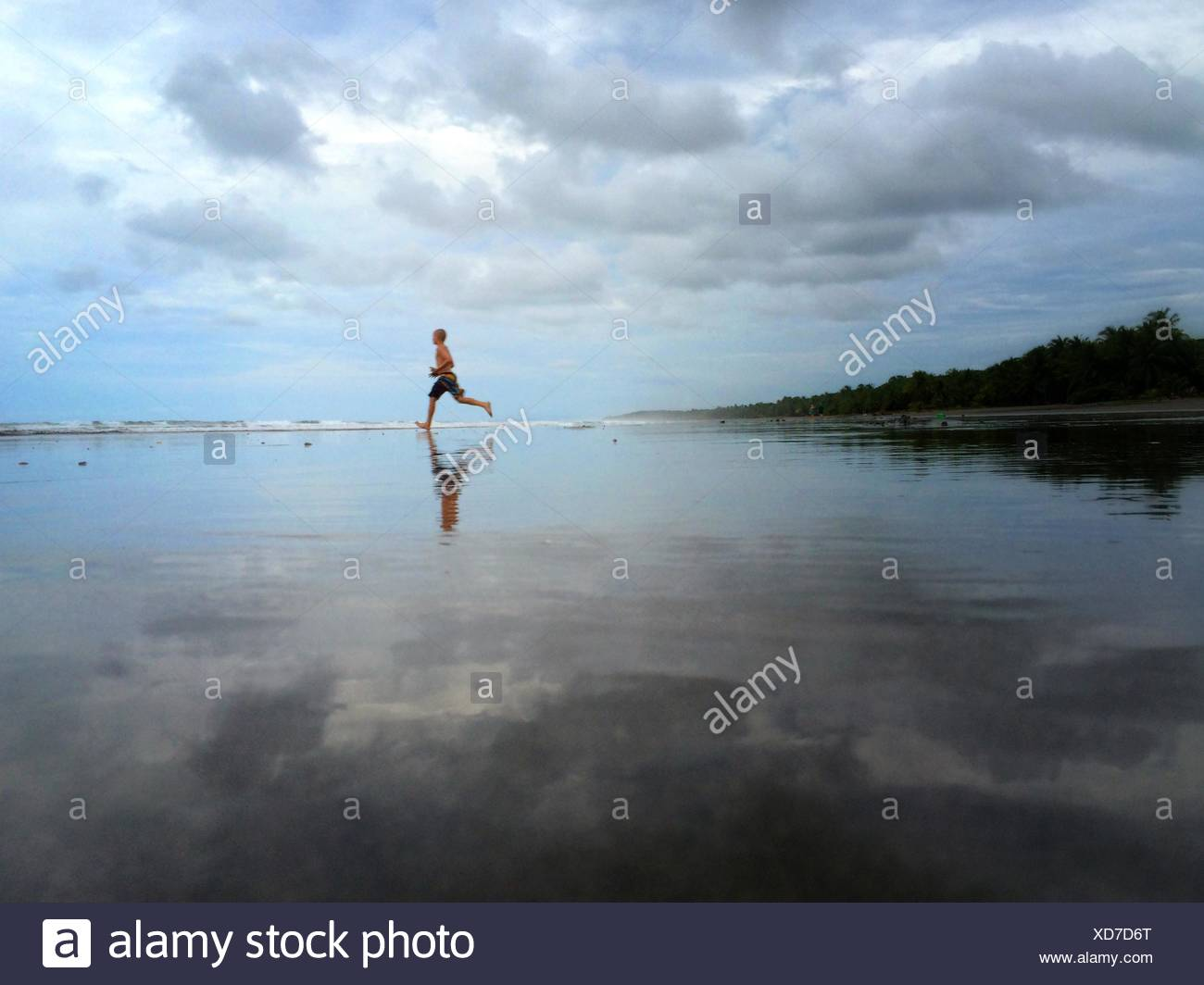 Boy running on beach Photo Stock