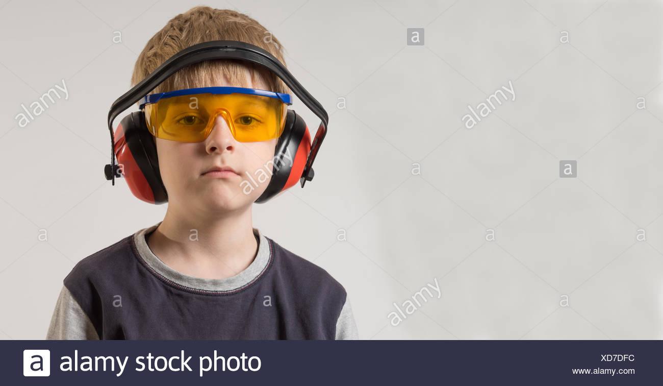 Portrait d'un garçon portant des lunettes de sécurité et les protections auditives. Photo Stock