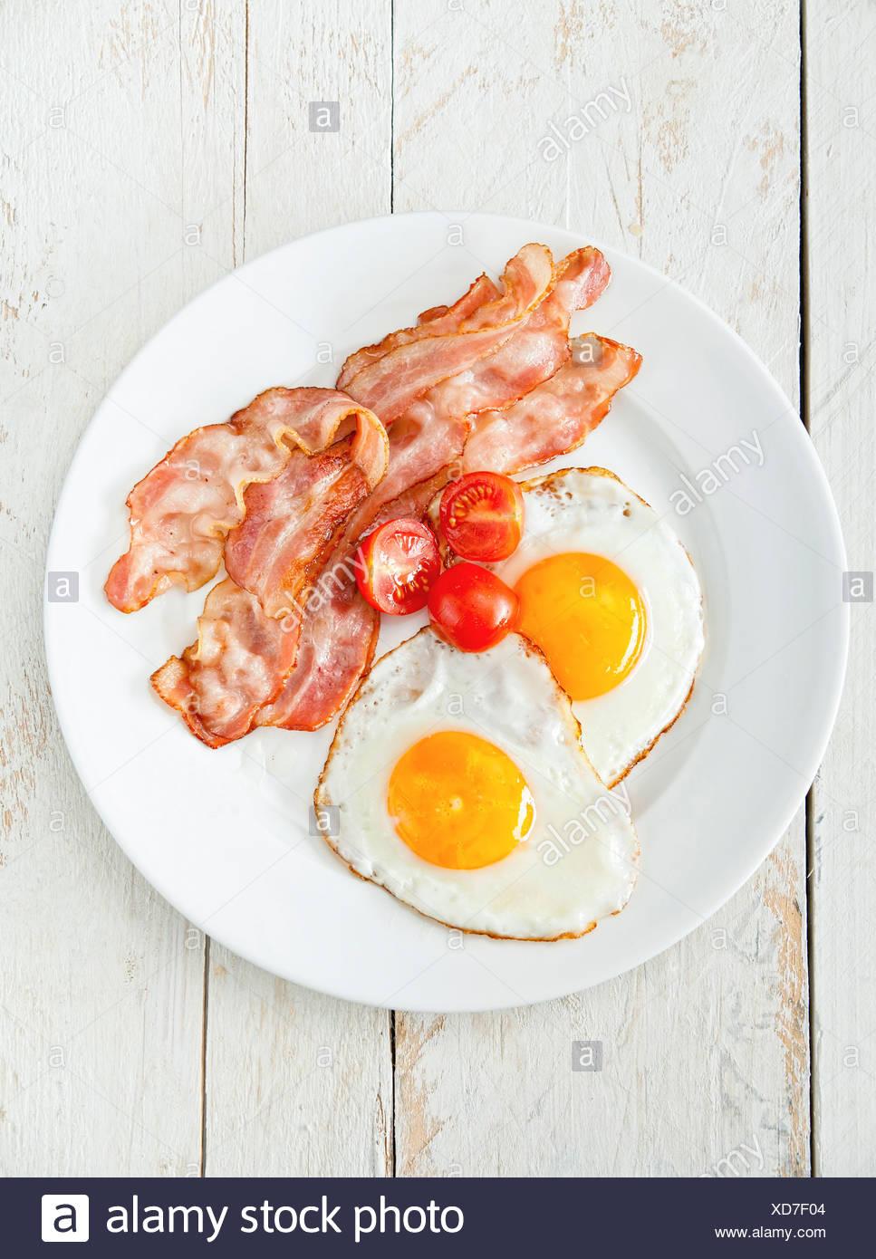 Des œufs et du bacon pour le petit déjeuner à la tomate Photo Stock