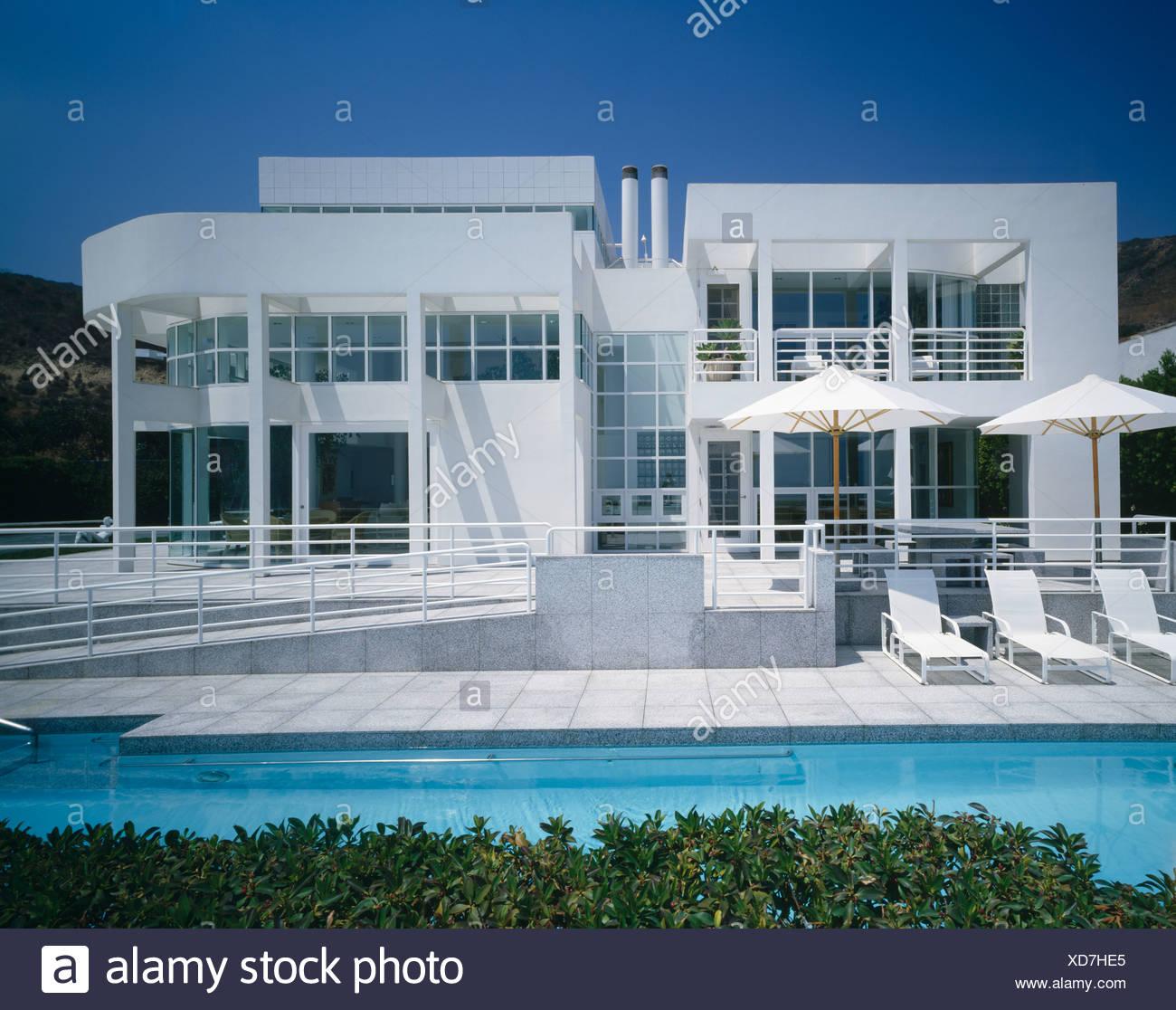 Des chaises longues et parasols blancs sur la terrasse au bord de ...