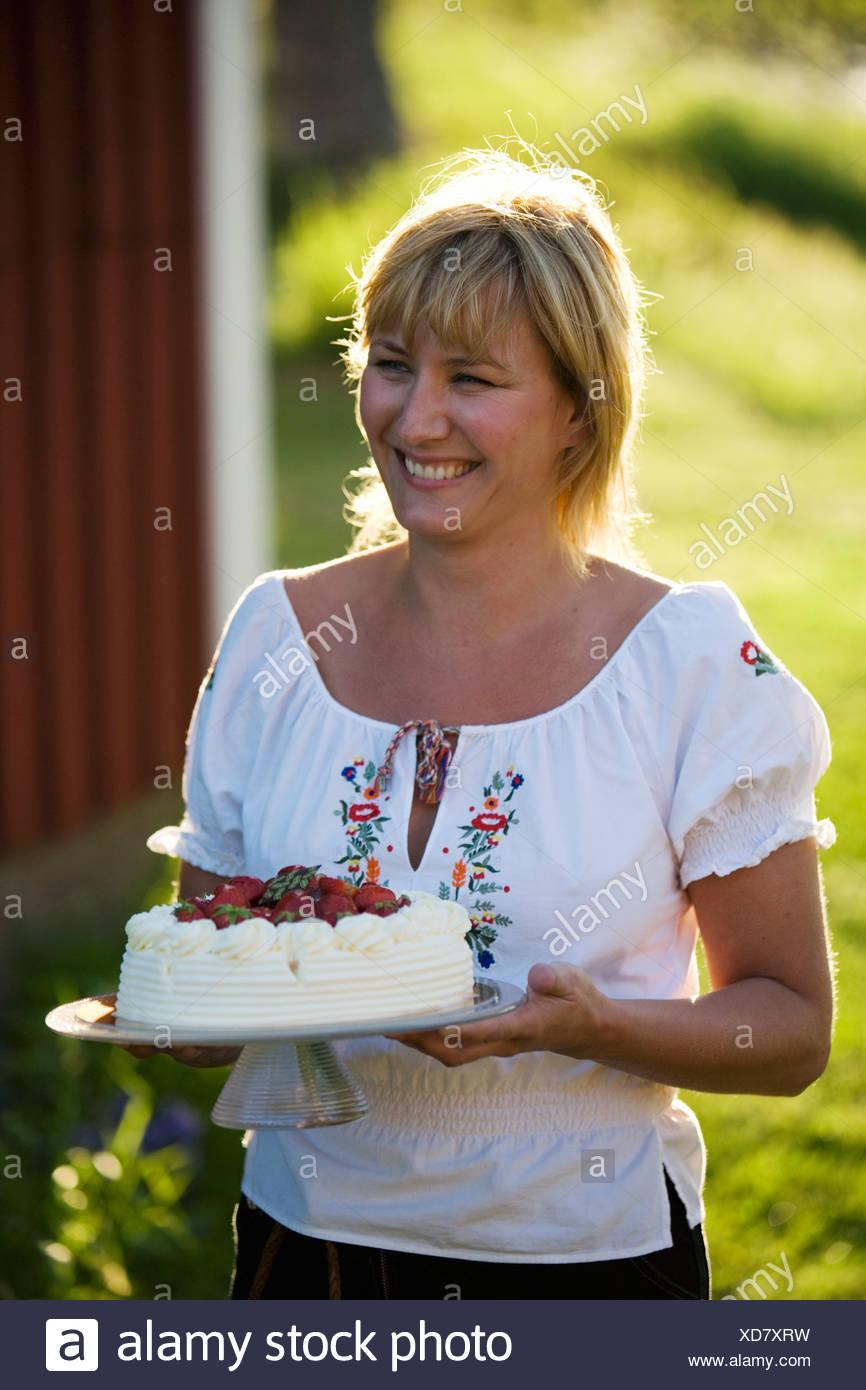 Une femme et un gâteau aux fraises, Fejan, archipel de Stockholm, Suède. Banque D'Images