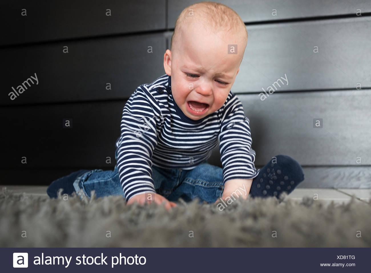 Bébé qui pleure garçon assis sur un tapis dans la salle de séjour Photo Stock