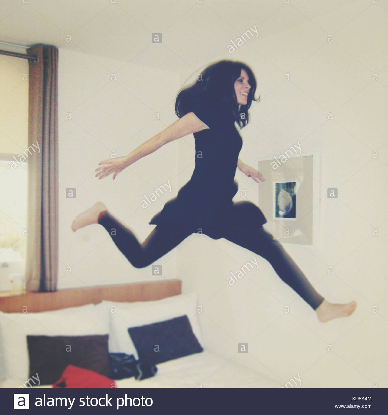 Young Woman Jumping on Bed At Home Banque D'Images