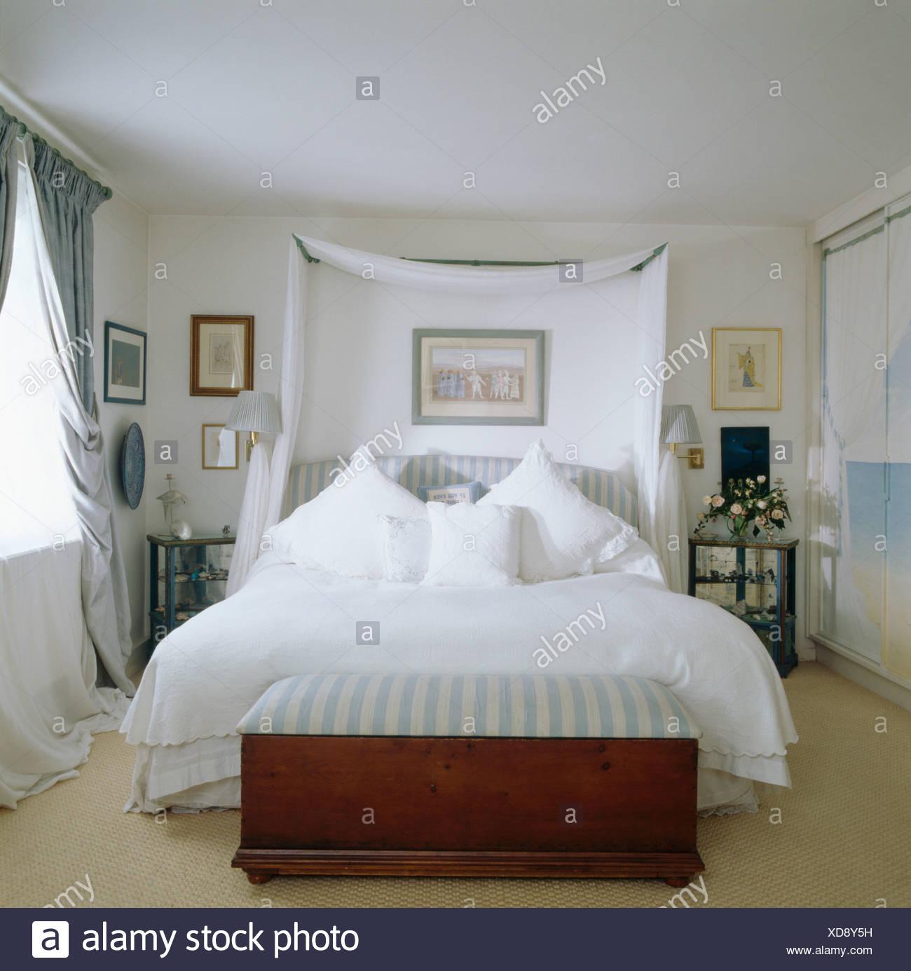Rideaux blancs au-dessus de lit avec draps et oreillers ...