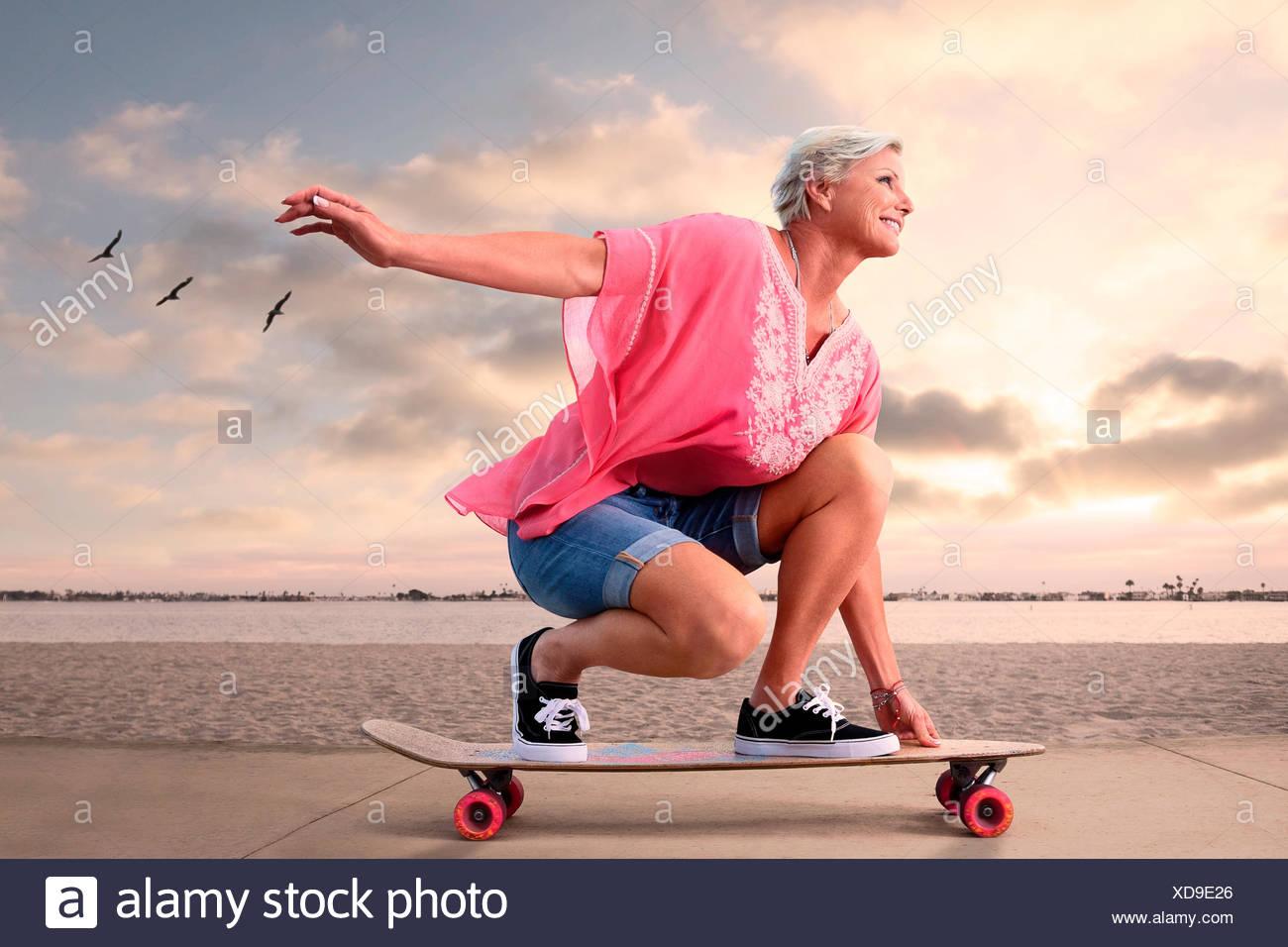 Jeune femme senior sur la planche à roulettes le long de plage au coucher du soleil, les oiseaux volant dans l'arrière-plan. Photo Stock