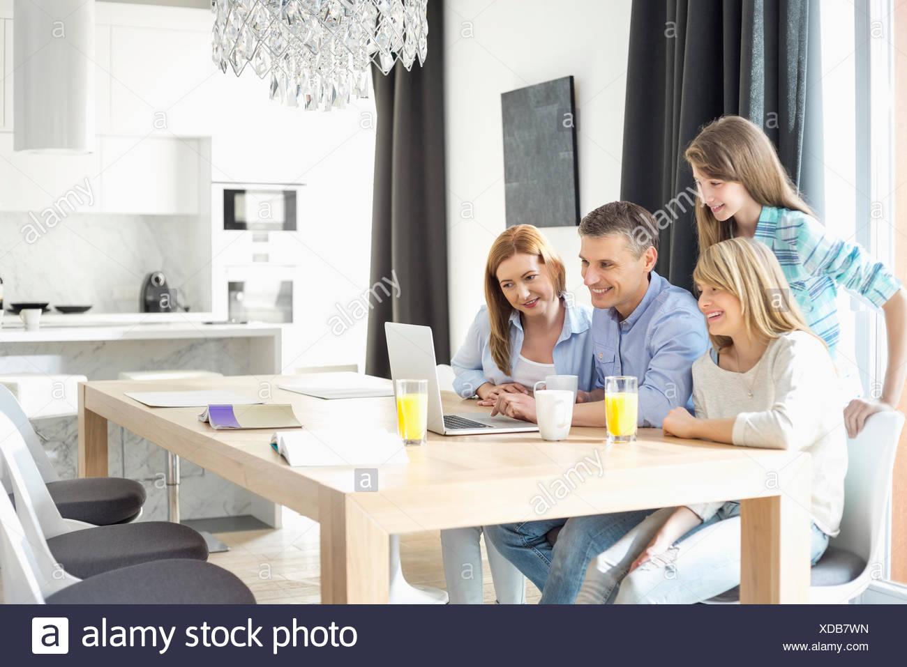 Famille heureuse de quatre à l'aide d'ordinateur portable à la maison Photo Stock