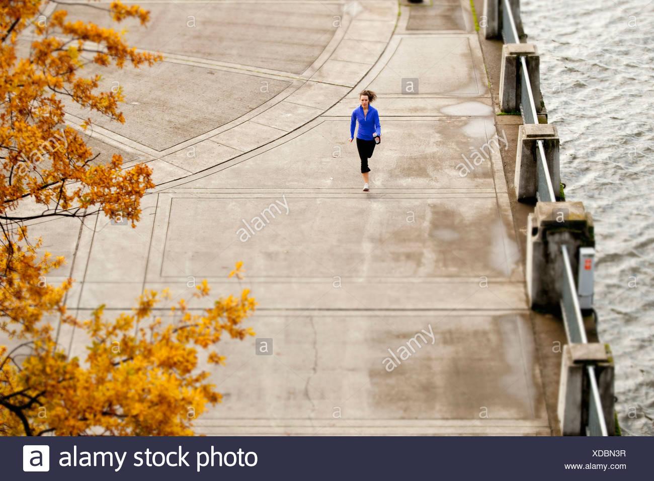 Une femme athlétique dans une veste bleue du jogging le long de la front de Portland, Oregon. Photo Stock