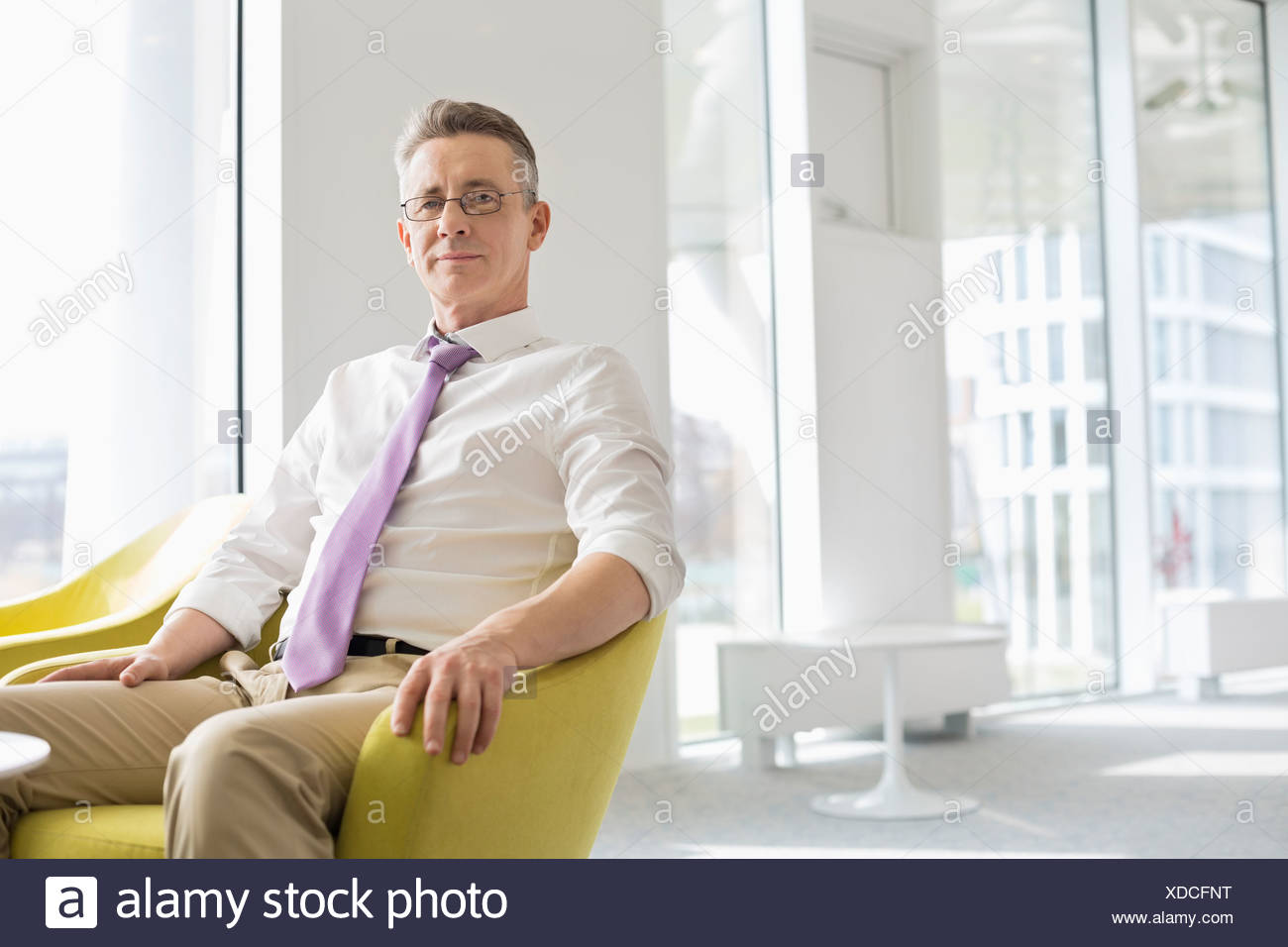 Portrait of businessman sitting at office lobby Photo Stock