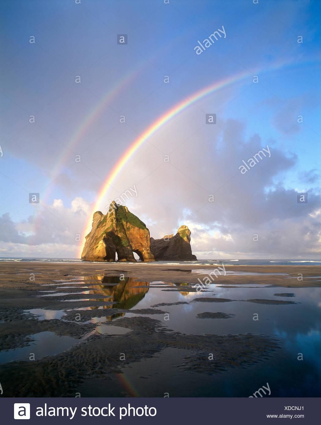 La Nouvelle-Zélande. arc-en-ciel sur 'Farewell Spit' beach et rock arch. île du sud. Photo Stock