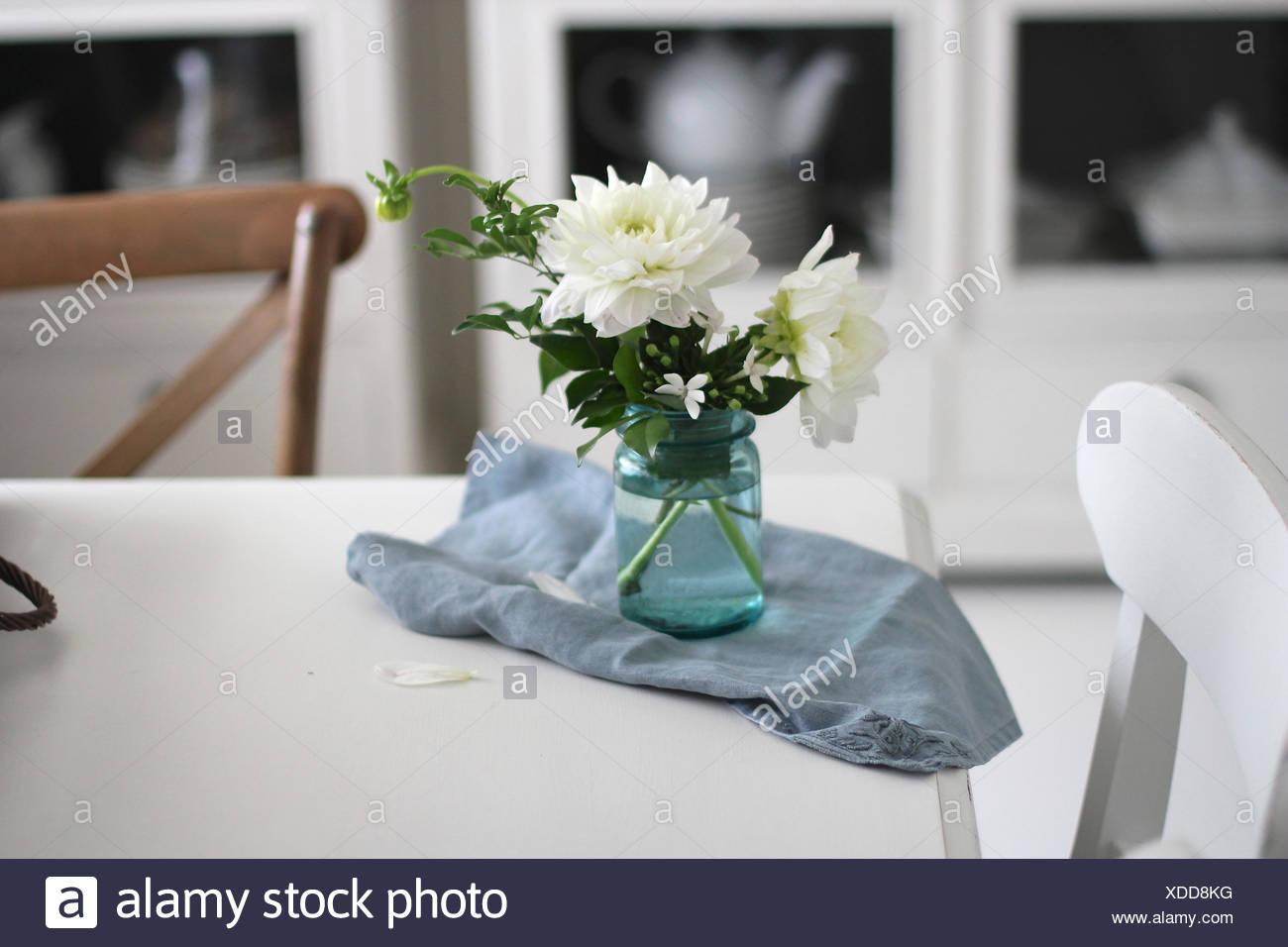 Vase de fleurs et une serviette sur la table de salle à manger Banque D'Images