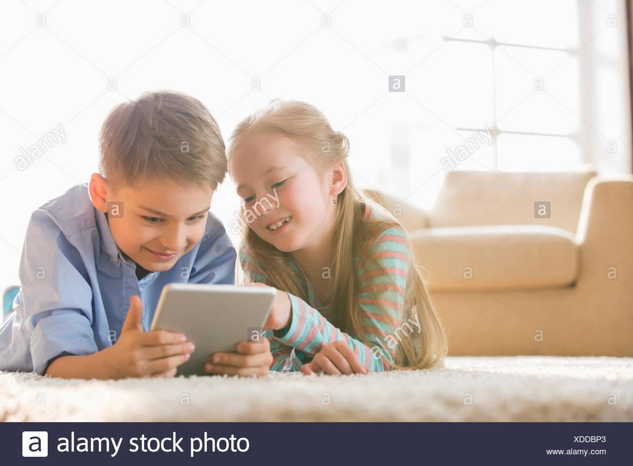 Brother and sister using digital tablet sur le plancher à la maison Banque D'Images