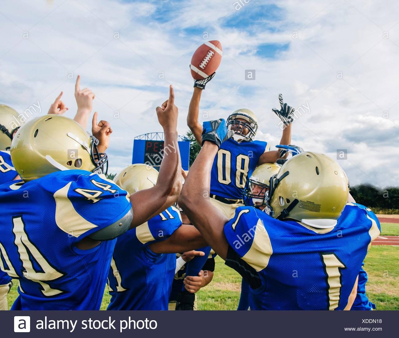 Les adolescentes et les jeunes équipes de football américain célébrant la victoire sur terrain de football Banque D'Images