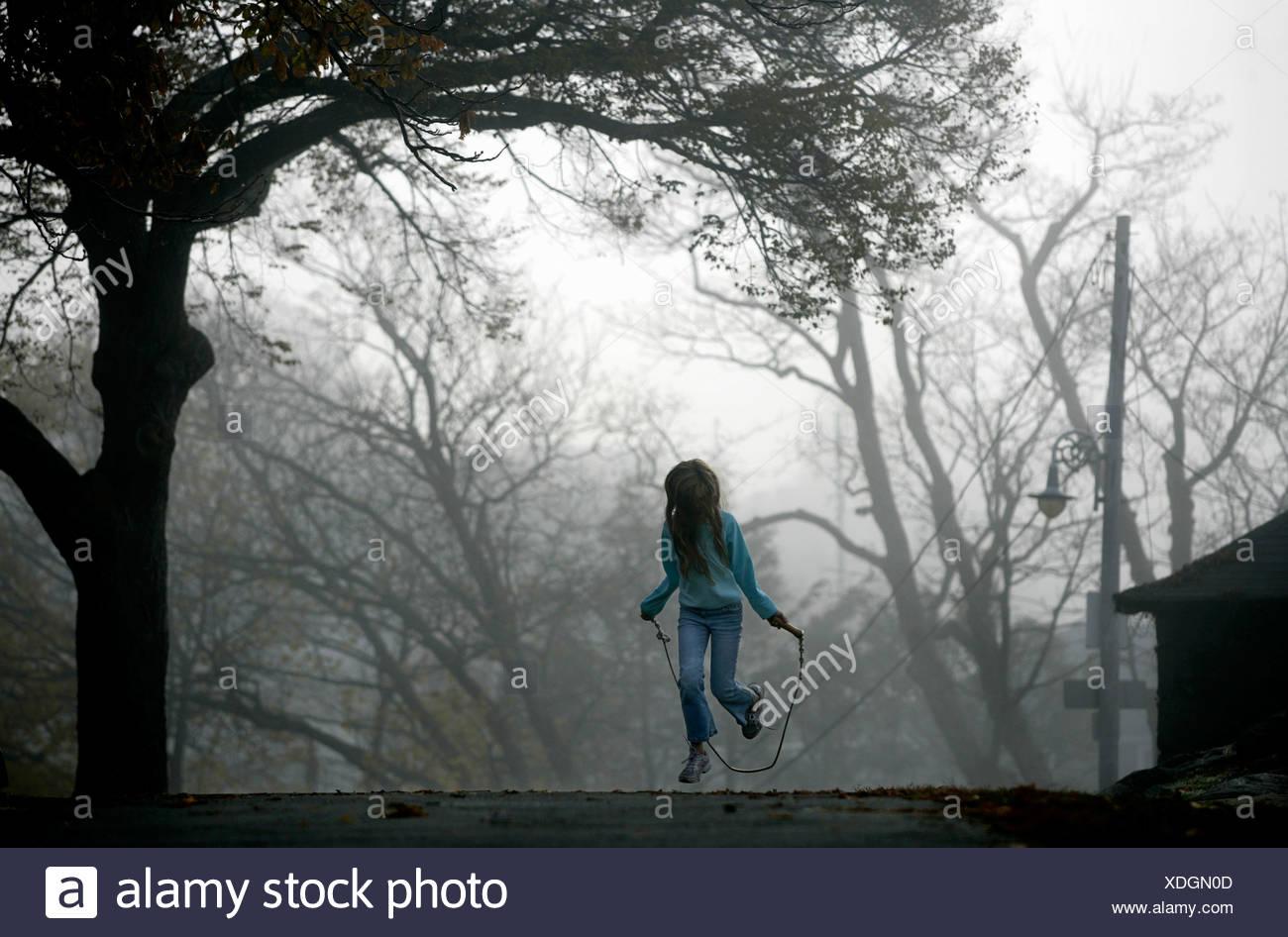 Une jeune fille saute à la corde. Banque D'Images