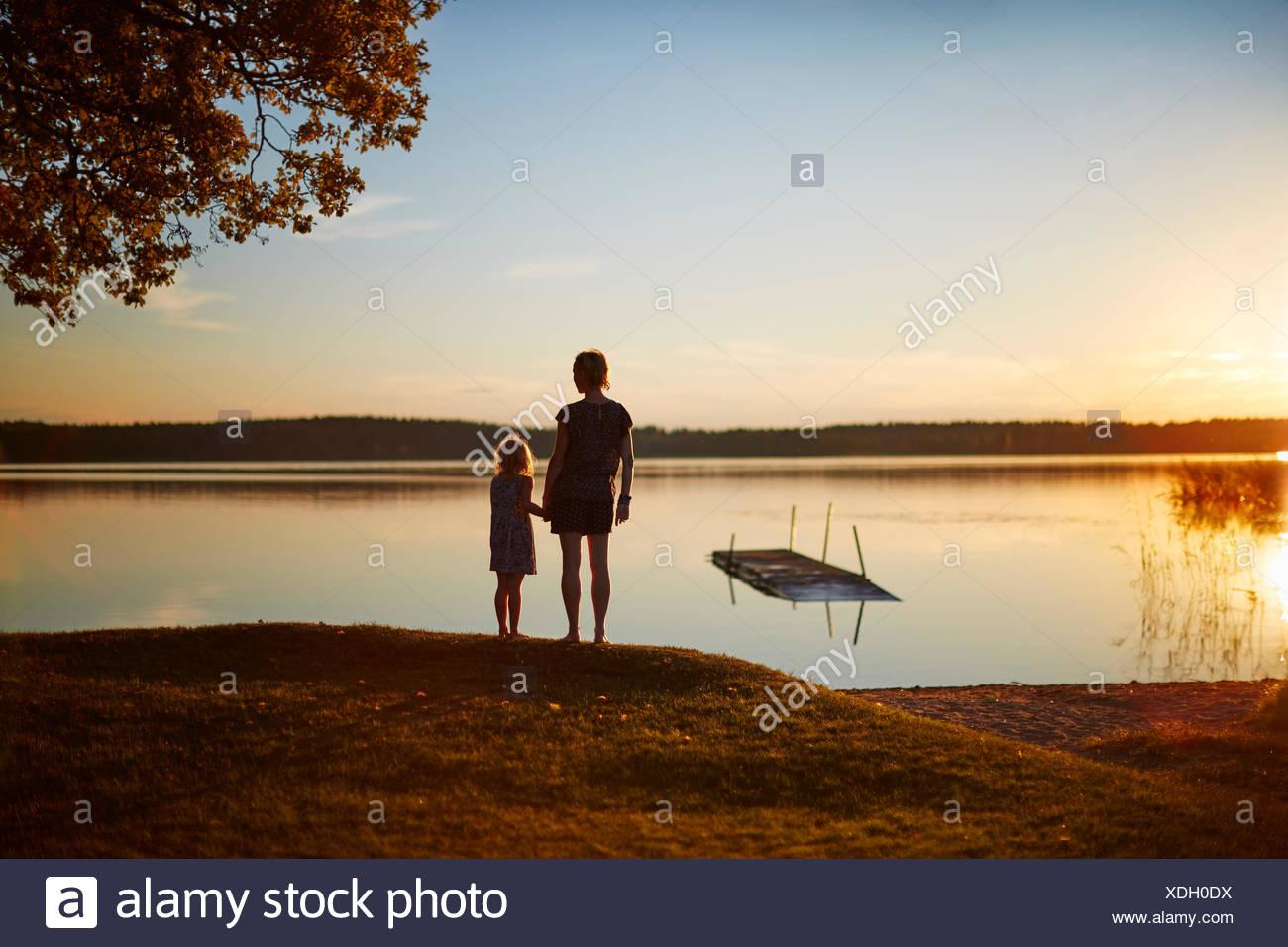 Mère et fille par le lac au coucher du soleil Photo Stock