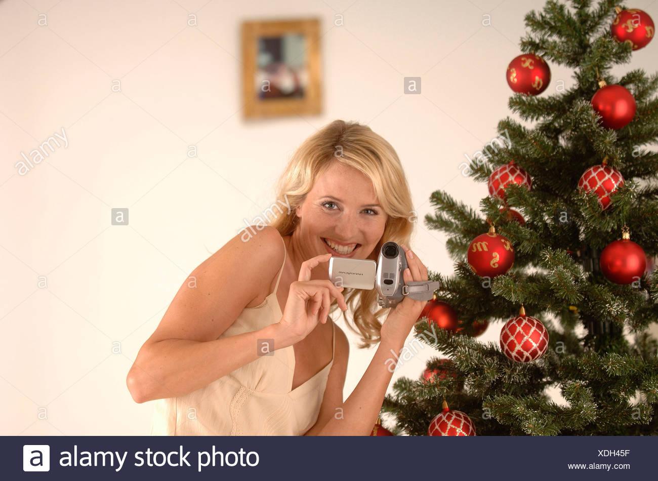 Femme blonde, 20-30, portant une robe de soirée lors du tournage avec un camescope en face d'un arbre de Noël Photo Stock