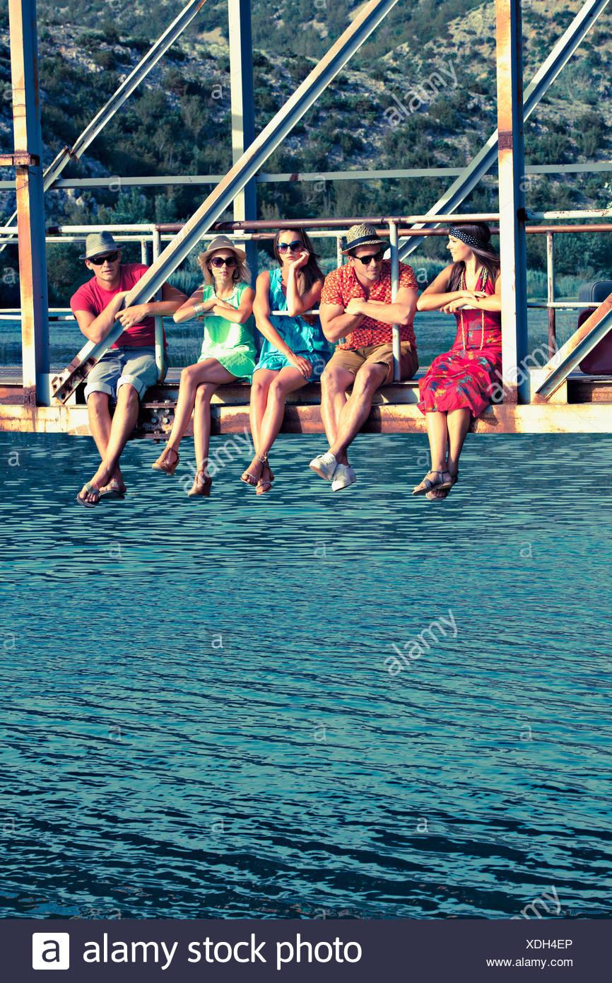 La Croatie, Dalmatie, de jeunes gens assis sur passerelle, côte à côte Photo Stock