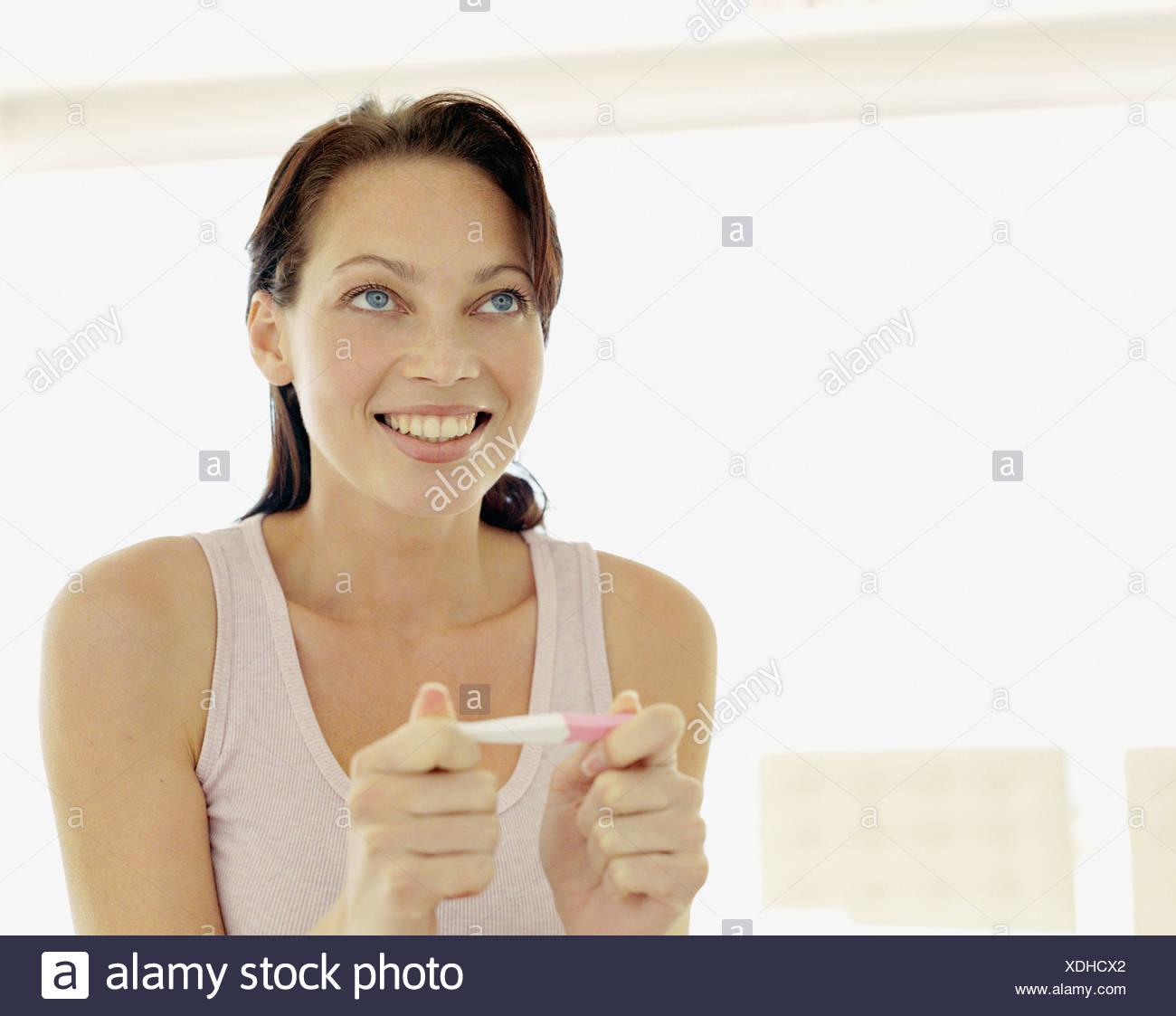 Une femme à la recherche à un test de grossesse Photo Stock