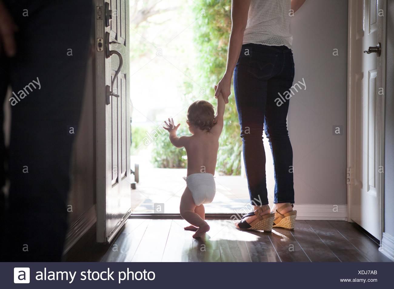 Vue arrière du mother holding baby boys mains debout à la porte avant ouverte Banque D'Images