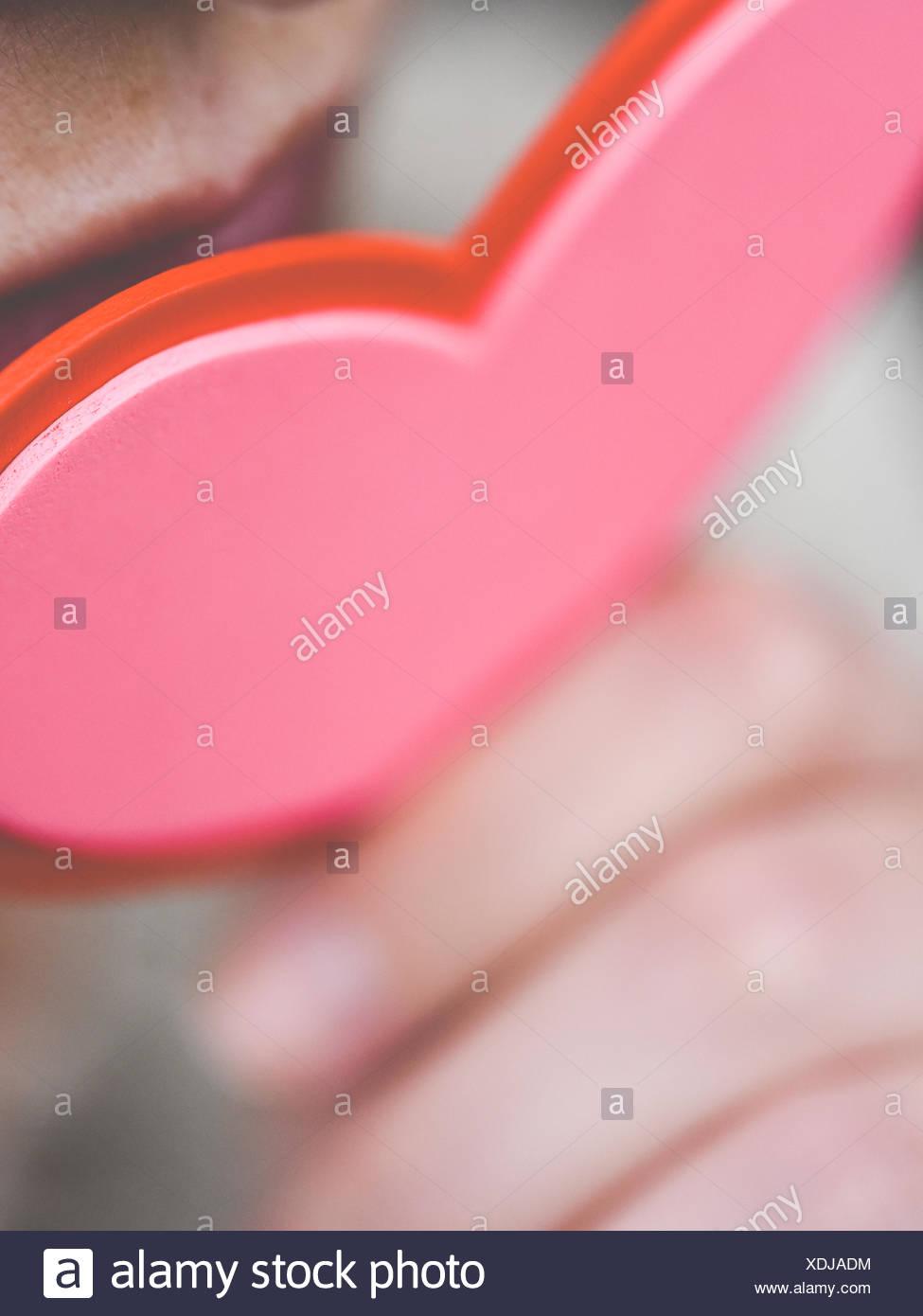 Femme tenant un cœur de papier près de sa bouche Photo Stock