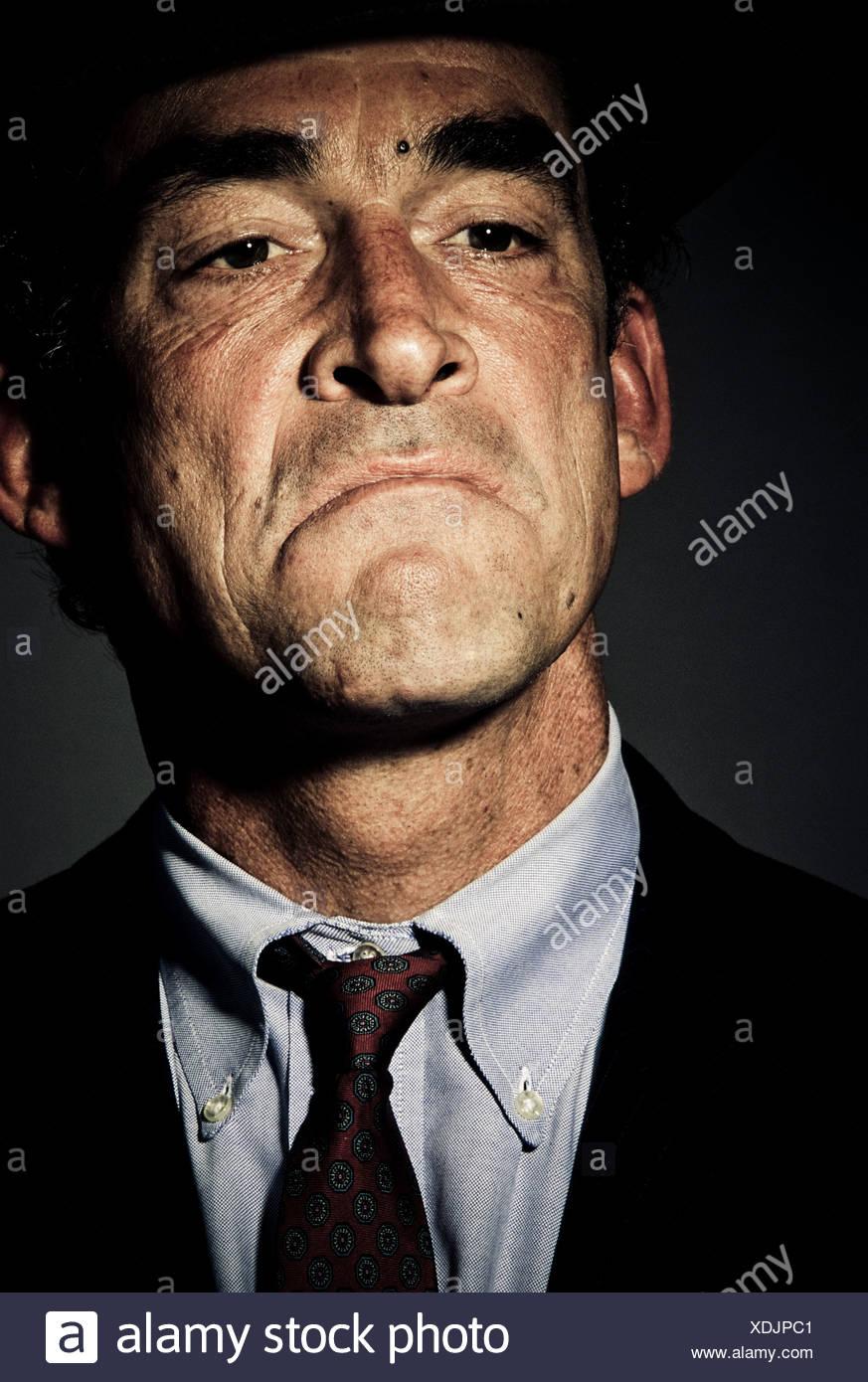 L'angle faible, Close up, vue de face d'un homme mûr dans un costume avec une expression sur son visage (portrait). Photo Stock