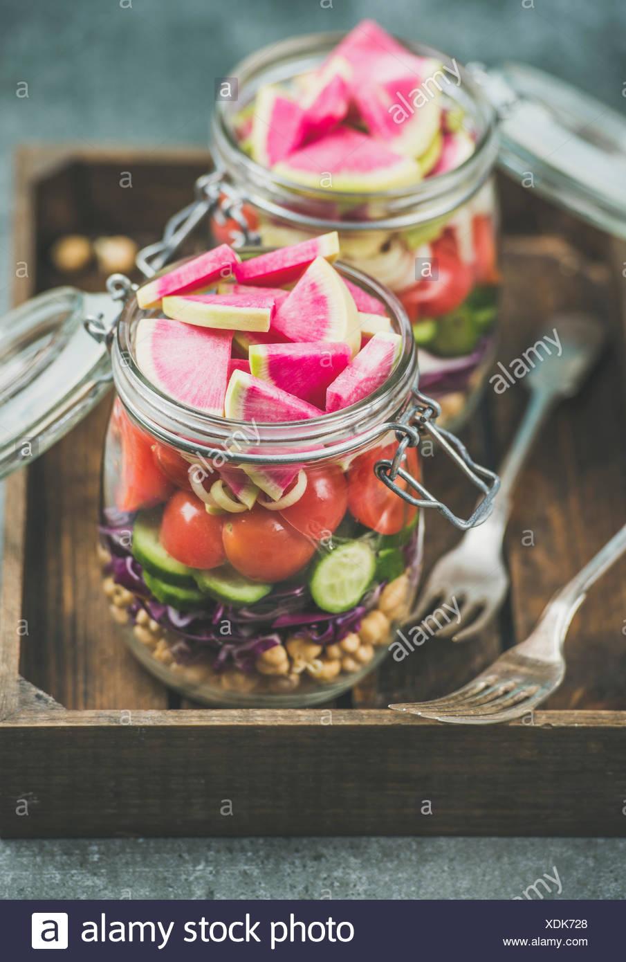 Déjeuner à emporter en bonne santé. Les légumes et les germes de pois chiches salade vegan dans des bocaux en verre dans le bac en bois, béton gris background, selective focus. Nettoyer Photo Stock