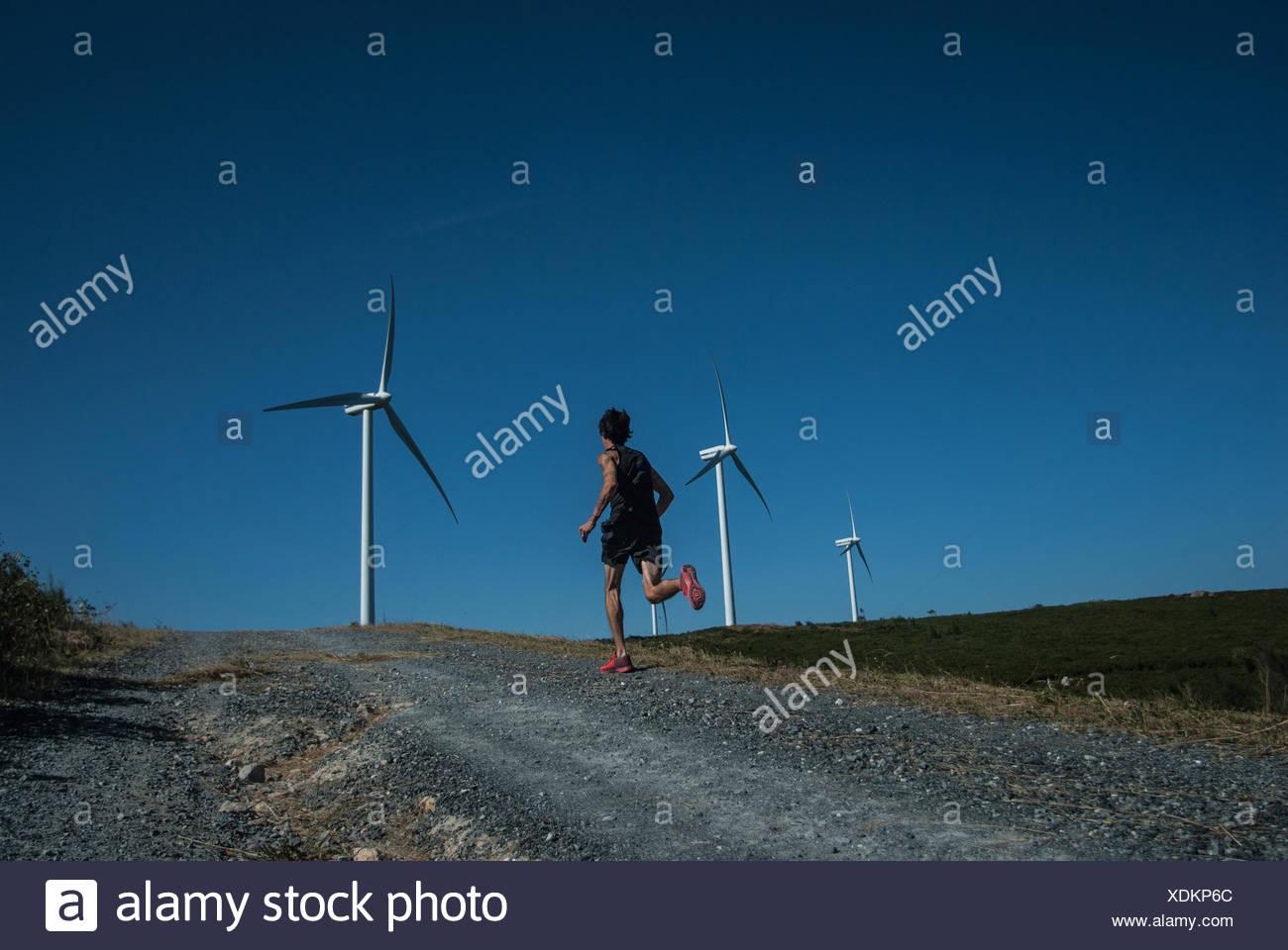 Mid adult man jogging on road, les éoliennes à distance Photo Stock