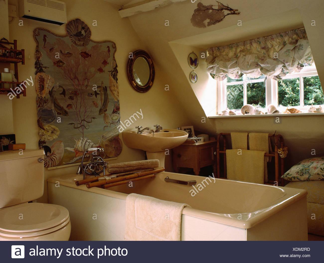 Baignoire rose et toilettes dans salle de bains mansardée avec ...
