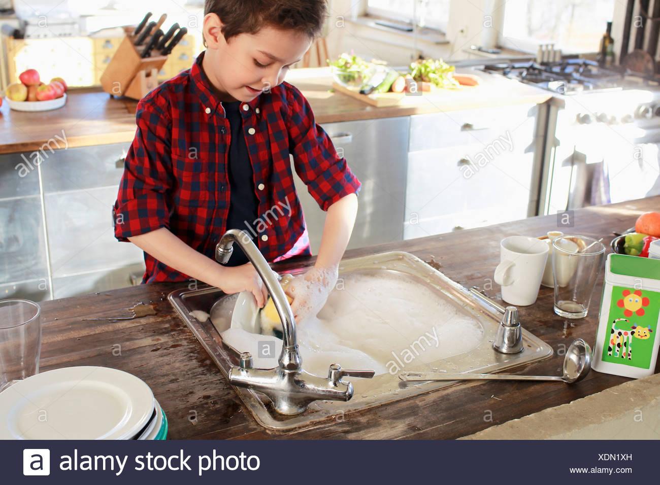 Jeune garçon dans la cuisine vaisselle Photo Stock