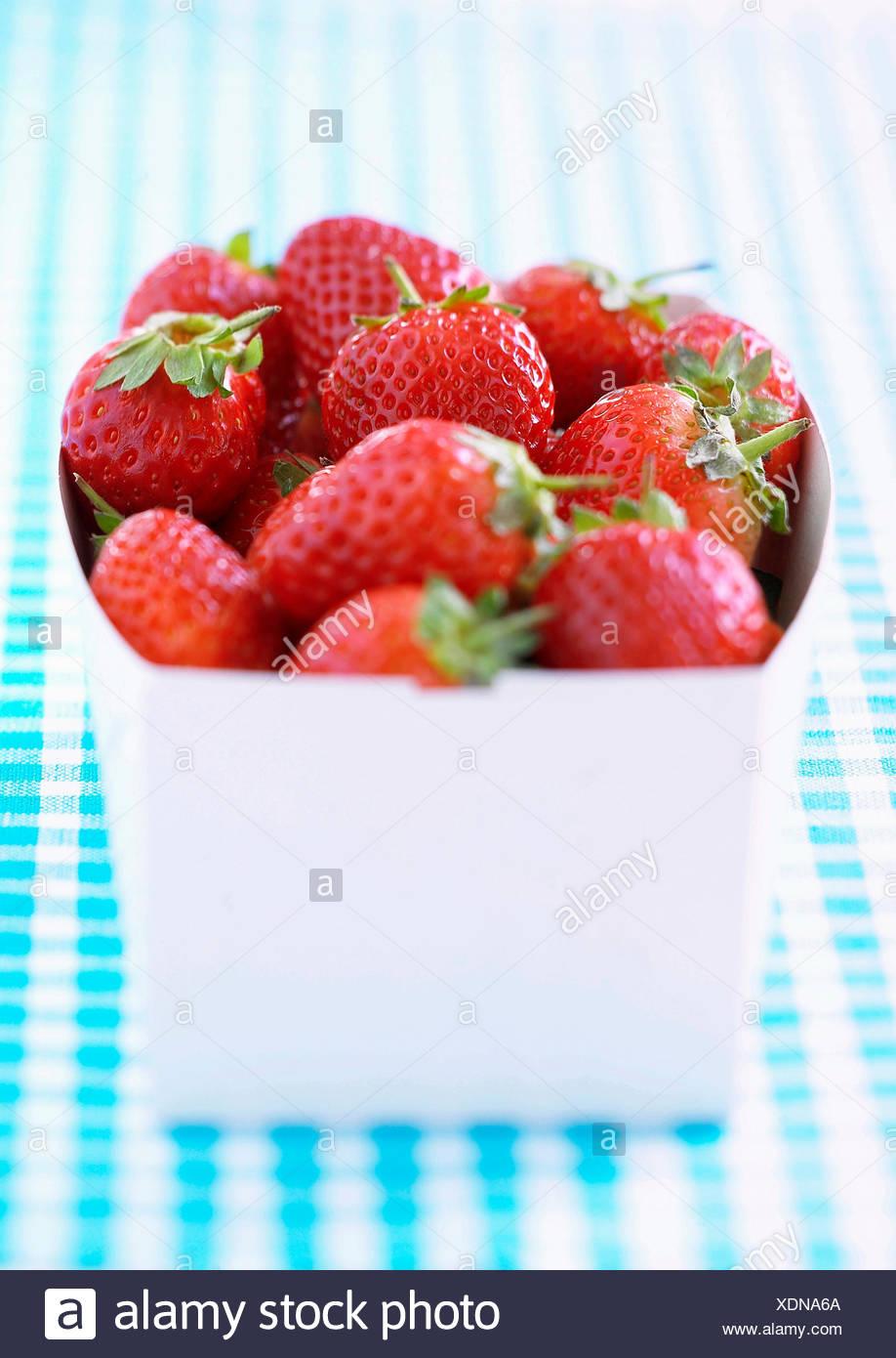 Fraise, Fragaria x ananassa, Studio shot de fruit rouge dans le récipient. Photo Stock