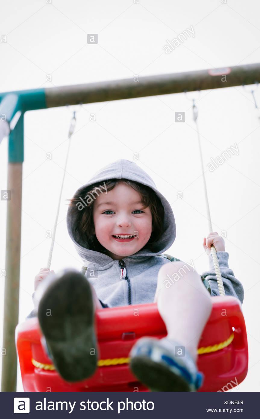 Un garçon dans un molleton à capuchon, assis sur une balançoire Photo Stock