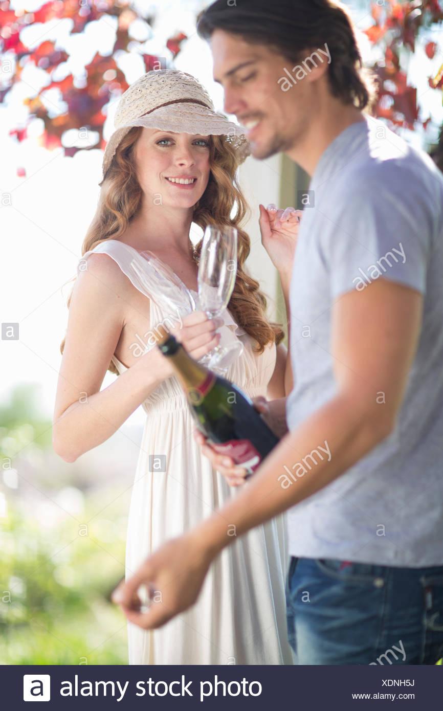 Couple prépare à célébrer avec champagne dans garden bar à vin Photo Stock