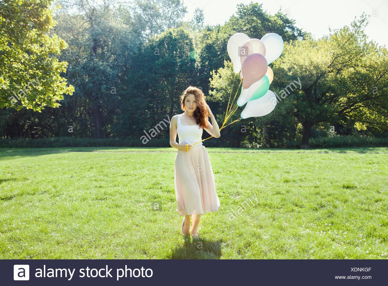Portrait de jeune femme timide dans park holding a bunch of balloons Photo Stock